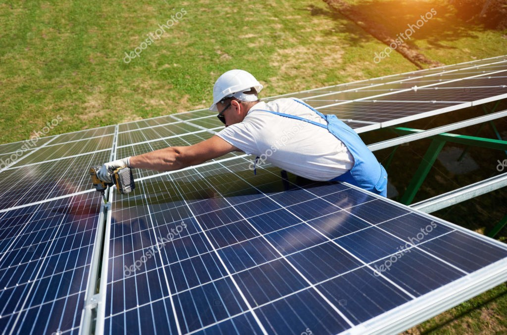 Wearing protective helmet, mounter installing solar panels on roof.